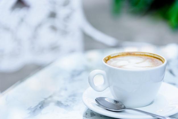 Una taza blanca de café y laptop lista para trabajar en la mañana.