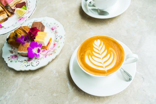 Taza blanca con café con leche y pastel