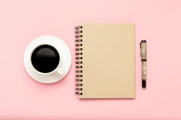 Taza blanca con café negro, cuaderno, lápiz sobre un fondo rosa. vista plana, vista superior