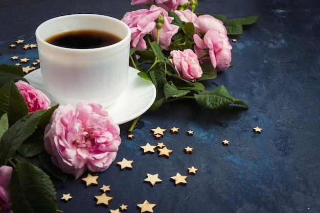 Taza blanca con café negro, estrellas y rosas rosadas sobre una superficie azul oscura