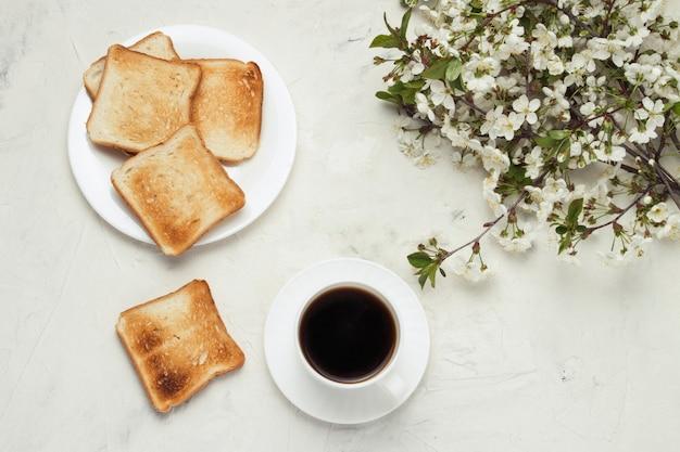 Taza blanca con café negro, pan tostado, jem y flores de primavera en el fondo de piedra clara. concepto de un desayuno saludable. vista plana, vista superior