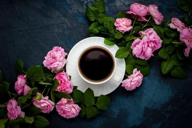 Taza blanca con café negro y rosas rosadas sobre una superficie azul oscuro