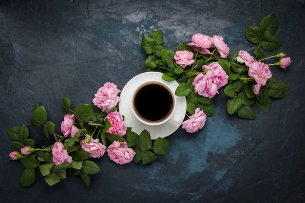 Taza blanca con café negro y rosas rosadas en una superficie azul oscura. vista plana, vista superior