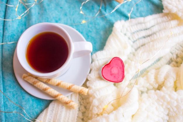Taza blanca con café o té y un corazón rojo