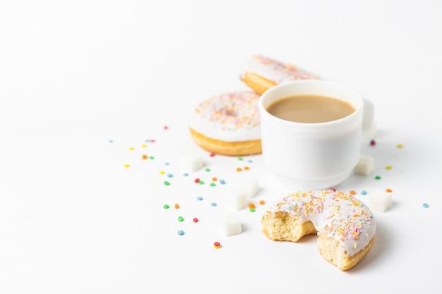 Taza blanca, café o té con leche y deliciosas donas frescas, dulces dulces decorativos multicolores sobre un fondo blanco. concepto de panadería, pasteles frescos, delicioso desayuno, comida rápida.