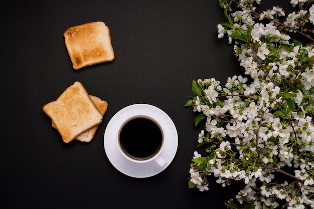 Taza blanca con café y tostadas, flores de primavera, rama de cerezo sobre un fondo oscuro.