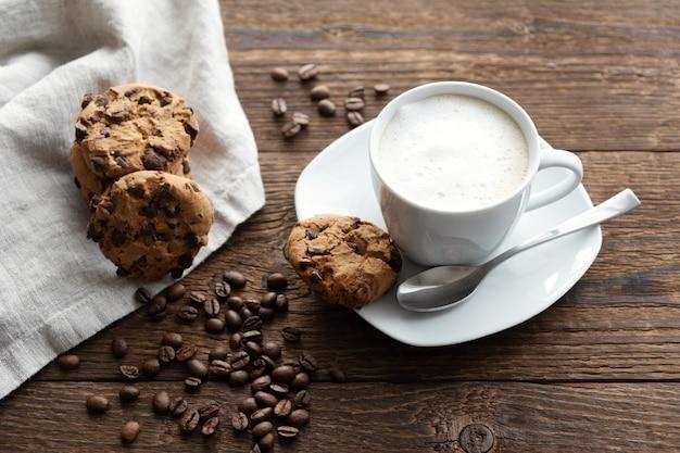 Una taza blanca de capuchino, café con espuma en un plato, granos de café y galletas galletas cerca.