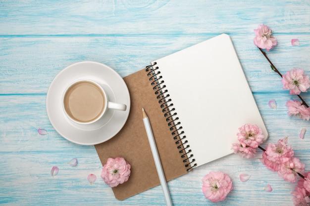 Taza blanca capuchino con flores de sakura, cuaderno en una mesa de madera azul