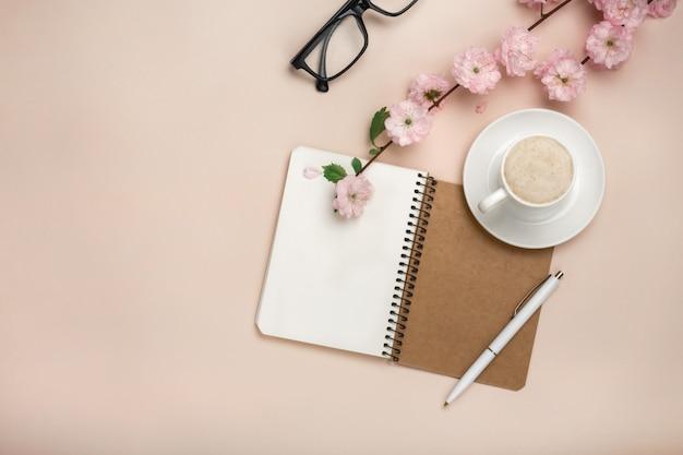 Taza blanca con capuchino, flores de sakura, cuaderno sobre un fondo rosa pastel