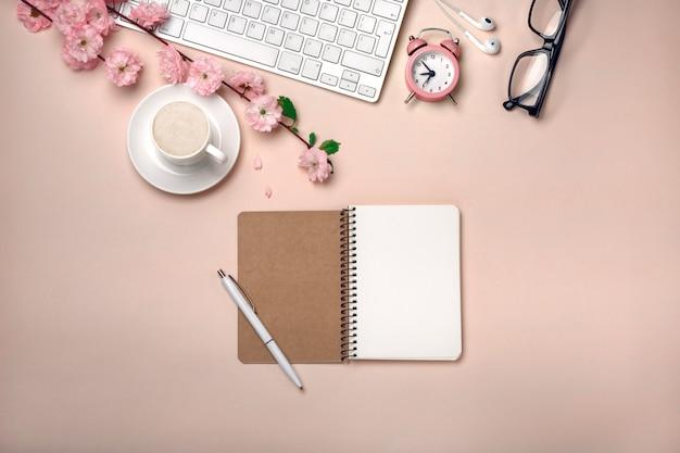 Taza blanca con capuchino, flores de sakura, teclado, reloj despertador, cuaderno sobre un fondo rosa pastel.