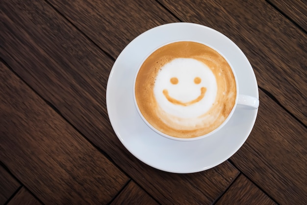 Taza blanca de la cara feliz de la sonrisa del arte del latte en fondo de madera marrón de la tabla.