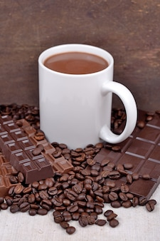 Taza blanca de chocolate caliente en granos de café y chocolate centrico
