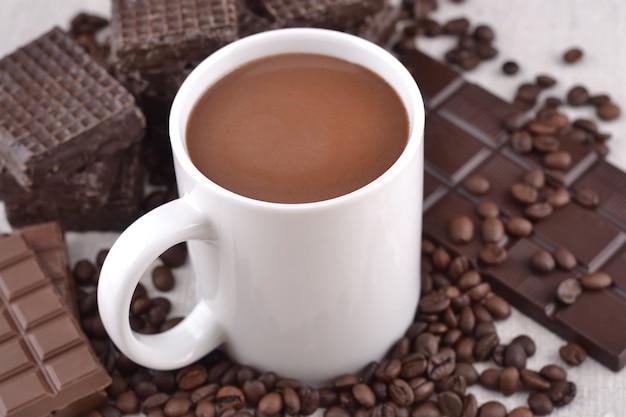Taza blanca de chocolate caliente sobre fondo de chocolate y granos de café