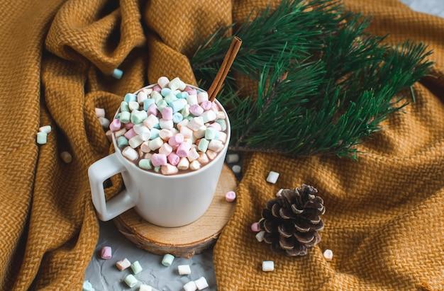 Taza blanca de chocolate caliente, tela escocesa amarilla, cono, rama de pino, abeto, malvaviscos coloridos, invierno, navidad