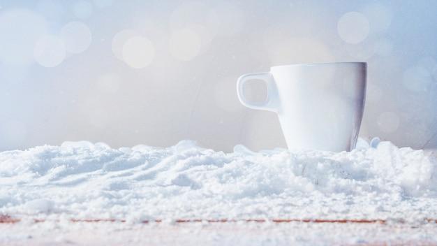 Taza blanca colocada sobre la nieve.
