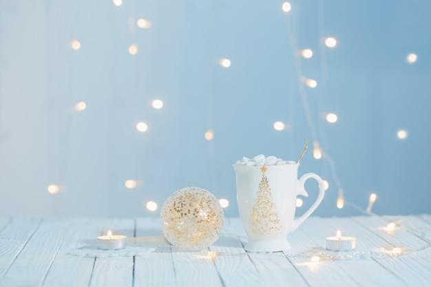 Taza blanca con decoraciones doradas en mesa de madera blanca
