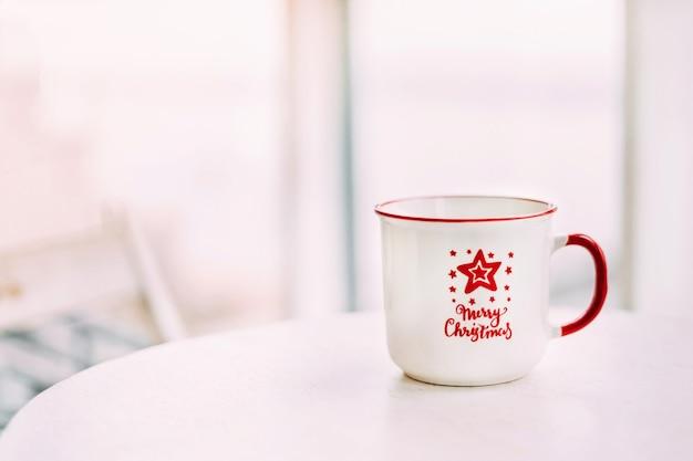 Taza blanca de enfoque suave con texto en rojo y una estrella de navidad sobre la mesa junto a la ventana. fondo borroso. foto horizontal. lugar para el texto.