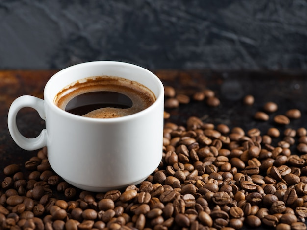 Taza blanca de espresso con granos de café tostados