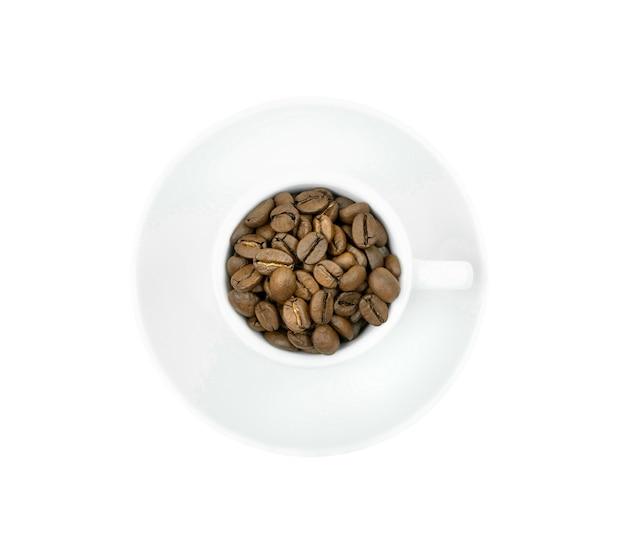 Una taza blanca con granos de café se aísla en un fondo blanco. vista superior