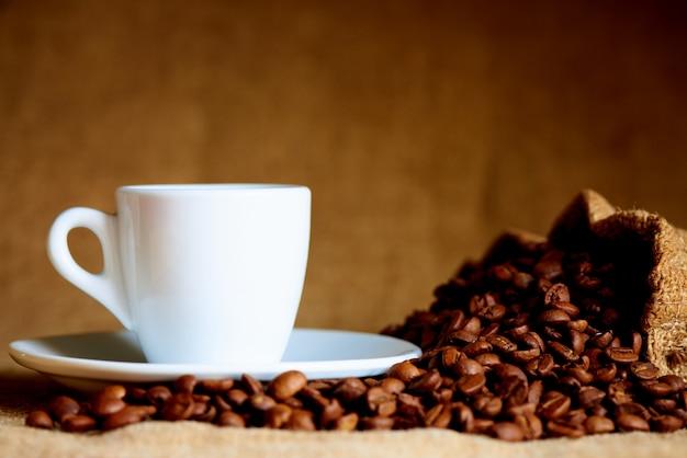 Taza blanca y granos de café en borrosa.