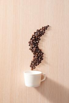 Una taza blanca con granos de café con forma de humo sobre la superficie de madera