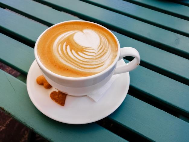 Taza blanca de latte con arte en de madera verde. espuma de arte, tazas de cerámica blanca.