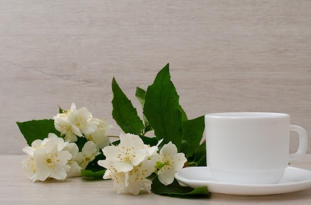 Taza blanca con una ramita de jazmín, primer plano