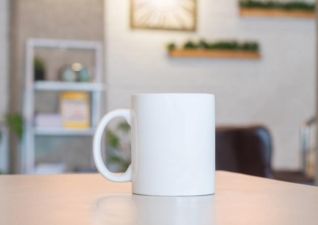 Taza blanca sobre mesa y fondo habitación moderna.