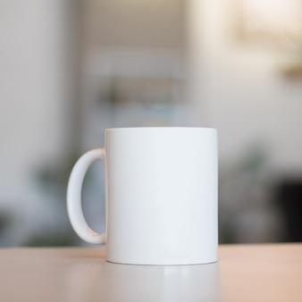 Taza blanca en la tabla y el fondo moderno del sitio. copa bebida en blanco para su diseño.