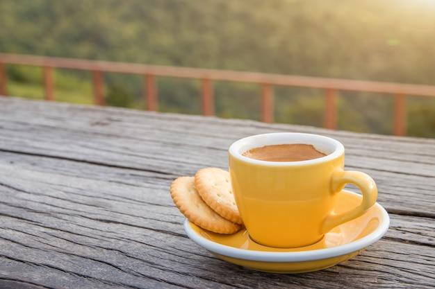 Una taza blanca de tazas de café exprés calientes colocadas con galletas en un piso de madera con niebla matutina y montañas con fondo de sol, mañana de café