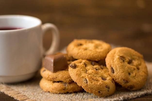 Taza blanca de té y galletas sobre fondo de madera oscura.