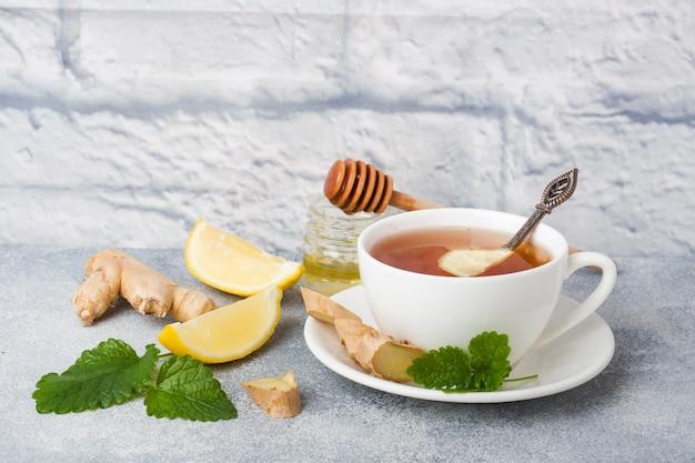 Taza blanca con té de hierbas natural jengibre limón menta y miel.