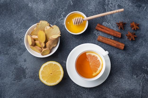 Taza blanca con té de hierbas natural jengibre limón y miel canela.
