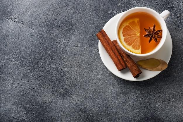 Taza blanca con té de hierbas natural con limón y canela.
