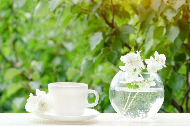 Taza blanca de té y un jarrón con jazmín.