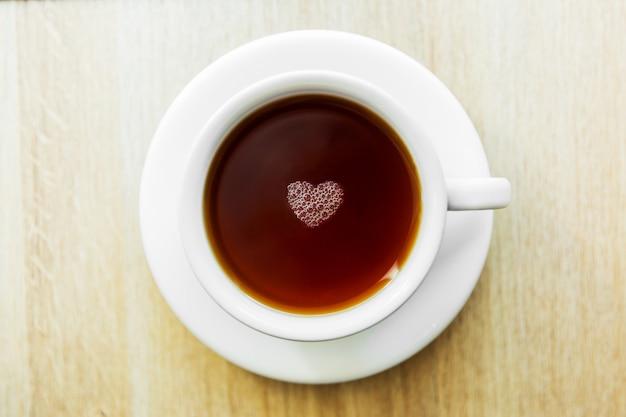 Taza blanca de té negro con burbujas en forma de corazón. taza blanca en mesa de madera