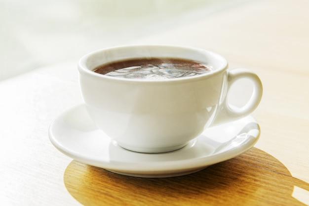 Taza blanca de té negro en la mesa de madera en un restaurante