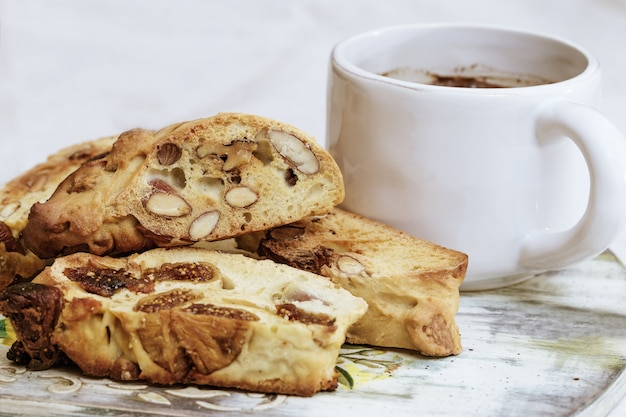Taza blanca con té negro y montón de galletas biscotti sobre fondo claro.