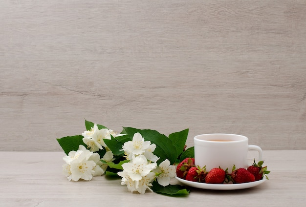Taza blanca con té, una rama de jazmín y fresa