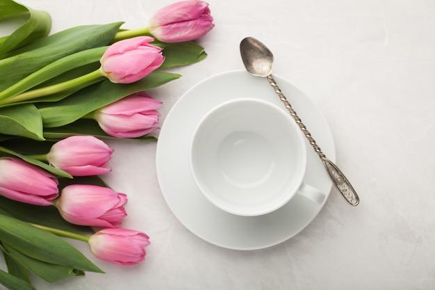 Taza blanca vacía de café y de tulipanes.