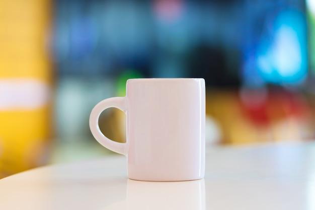 Taza en blanco sobre fondo blanco mesa y copyspace