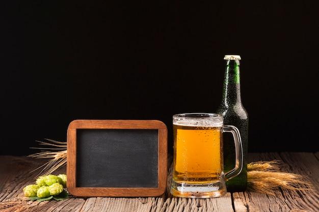 Taza y botella de cerveza sobre fondo de madera