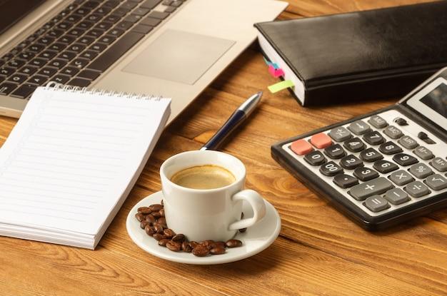 Una taza de buen café ayuda a trabajar con documentos. cuaderno, bolígrafo, computadora portátil, calculadora, documentos financieros, una taza de café capuchino sobre la mesa.