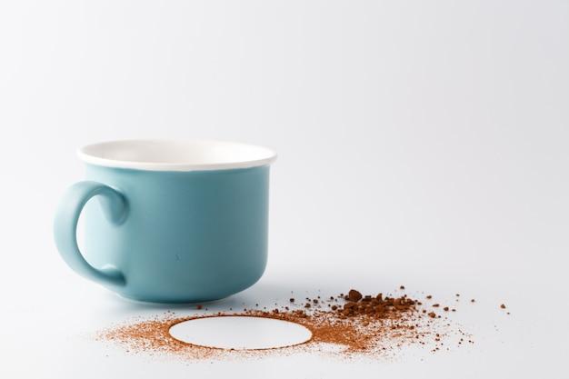 Taza de cacao y cacao en polvo sobre superficie blanca