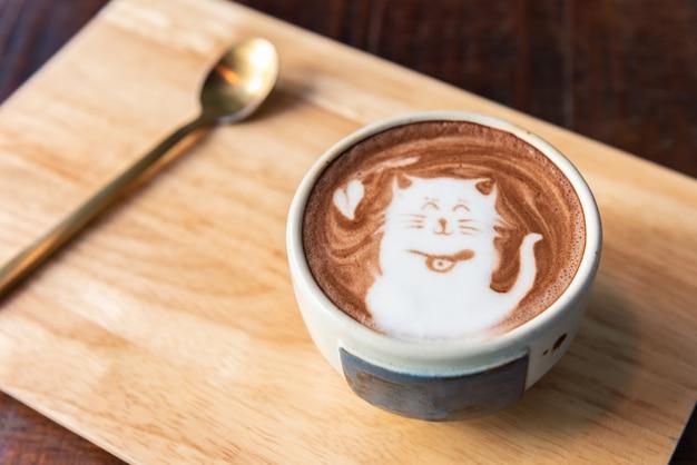 Taza de cacao caliente con forma de gato con cuchara en un plato de madera