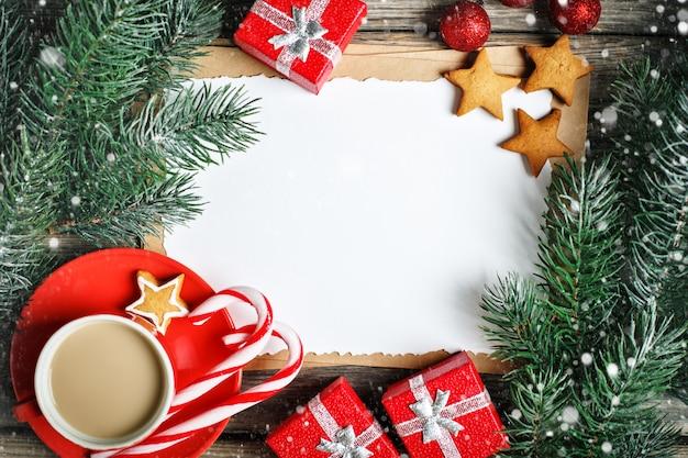 Taza de cacao, galletas, regalos y ramas de abeto en una mesa de madera.
