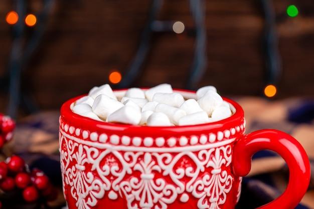 Taza con cacao y malvaviscos con acogedor fondo de luces de guirnalda de navidad
