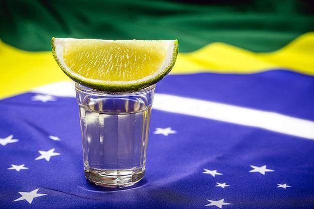 Taza de cachaã§a o pinga brasileña, con la bandera brasileña al fondo en celebración del día nacional de la cachaã§a