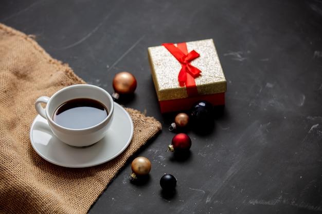Taza de café, adornos navideños y caja de regalo