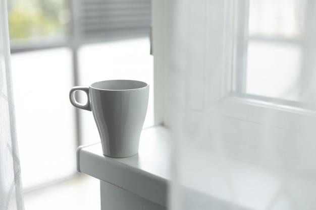 Una taza de café en el alféizar. ventana grande. estilo escandinavo. copia espacio
